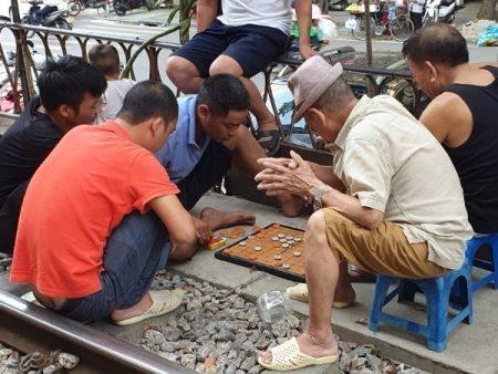 Men playing checkers on Train Street, Hanoi
