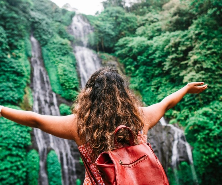 how to stay healthy while travelling - girl at waterfall
