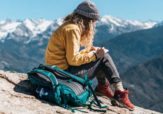 Travel Journal Prompts - Girl writing in travel journal sitting on a mountain